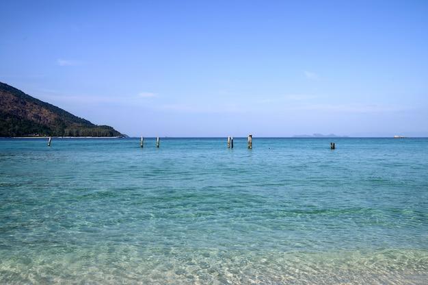 Tropisches kristallmeer mit pfosten und blauem himmel