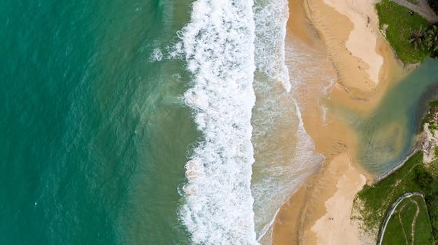 Tropisches meer und welle, die auf sandigem ufer am karon strand in der vogelperspektive-brummenkameraspitze phukets thailand unten zusammenstößt.