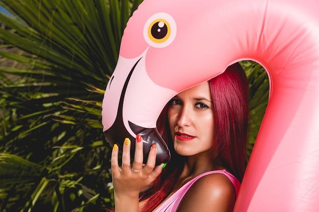 Tropisches porträt der schönheit mit rosa flamingo schwimmen