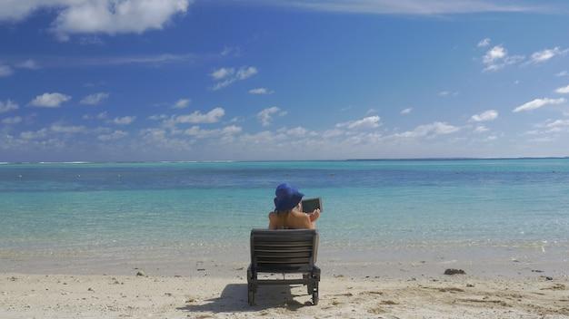 Tropisches resort und frau beim sonnenbaden mit tablet-computer