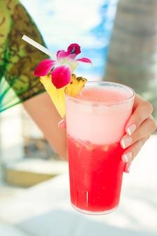 Tropisches rotes cocktail in der hand einer jungen frau auf einem exotischen erholungsort