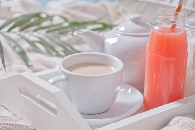 Tropisches sommerfrühstück mit tasse tee, teekanne und erfrischendem exotischem saft