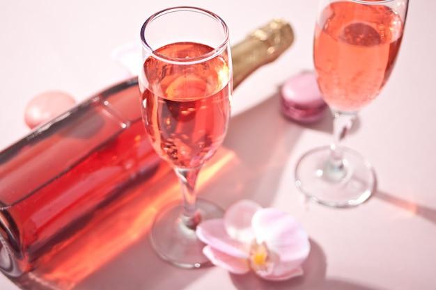 Tropisches sommerglas rosa cocktailwein-champagner mit flasche verzierten rosa orchideenblumen und makronen. ansicht von oben.
