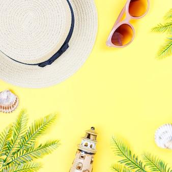 Tropisches sommerkonzept mit frauenmodeaccessoires, blättern und ananas auf gelbem hintergrund. flache lage, draufsicht