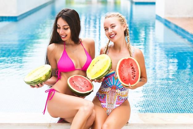 Tropisches sommerporträt von zwei hübschen jungen mädchen, die spaß nahe pool haben, zwei große wassermelonen nahe titten halten, überraschte grimassen, verrückte gefühle, helle bikinis, genießen sie urlaub.