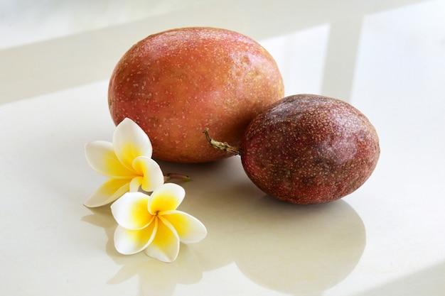 Tropisches stillleben mit passionsfrucht und frangipani-blüten