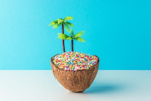 Tropisches strandkonzept aus kokosnuss mit süßer farbdekoration und palme auf blauem hintergrund