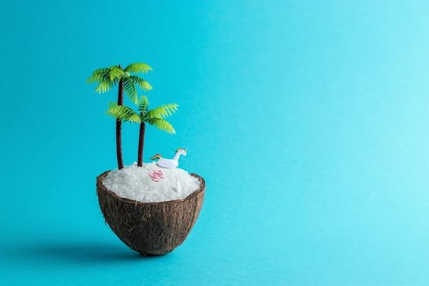 Tropisches strandkonzept gemacht von kokosnuss und palme auf blauem hintergrund
