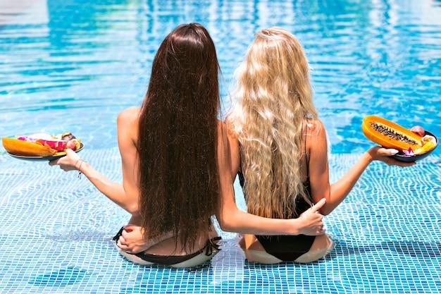 Tropisches urlaubsporträt für zwei langsame mädchen mit erstaunlich langen blonden und brünetten haaren, die sich vor der kamera zurücklehnen und fehlende bikinis tragen, die am pool posieren und teller mit exotischen früchten halten,