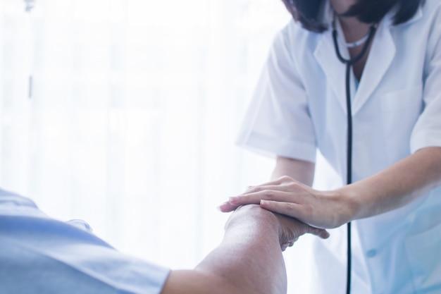 Trost- und ermutigungskonzeptdoktor, der hände des patienten hält