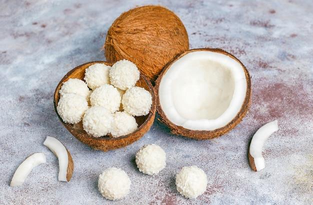 Trüffel aus kokosnuss und weißer schokolade mit halber kokosnuss
