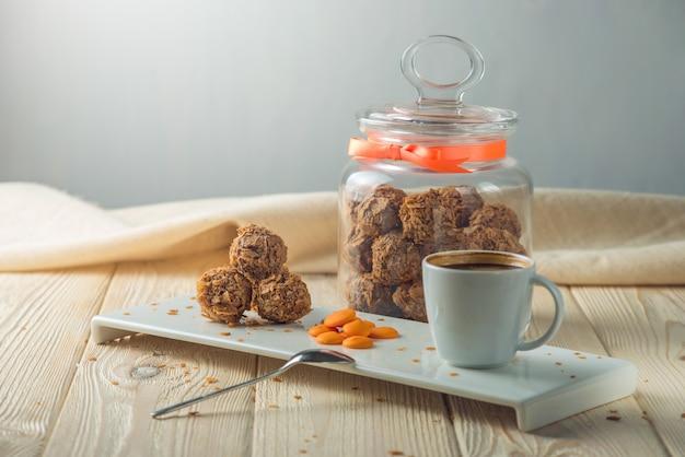 Trüffelbällchen mit orangenschokolade auf der untertasse neben dem bonbonglas und einer tasse kaffee.