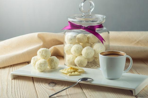 Trüffelbällchen mit weißer schokolade, bestreut mit kokosnuss, auf einer untertasse neben einem glas süßigkeiten und einer tasse kaffee