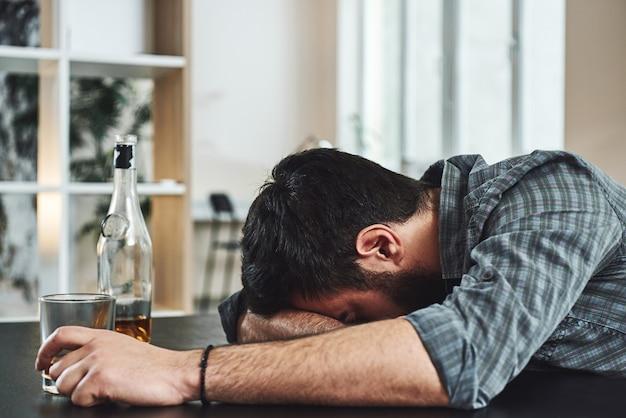 Trunkenheit ist vorübergehender selbstmord alkoholmissbrauch betrunkener mann liegt auf einem tisch mit glas