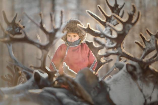 Tsaatan-junge, gekleidet in ein traditionelles kleid, mit einem rentier in einer taiga der nordmongolei
