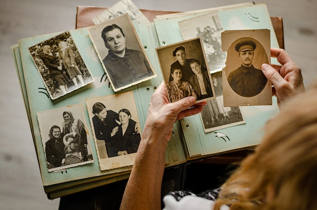 Tscherkassy / ukraine - 12. dezember 2019: weibliche hände halten und altes foto ihrer verwandten. vintage fotoalbum mit fotos. konzept der familien- und lebenswerte.