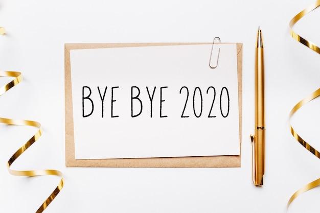 Tschüss 2020 notiz mit umschlag, stift, geschenken und goldband auf weiß.