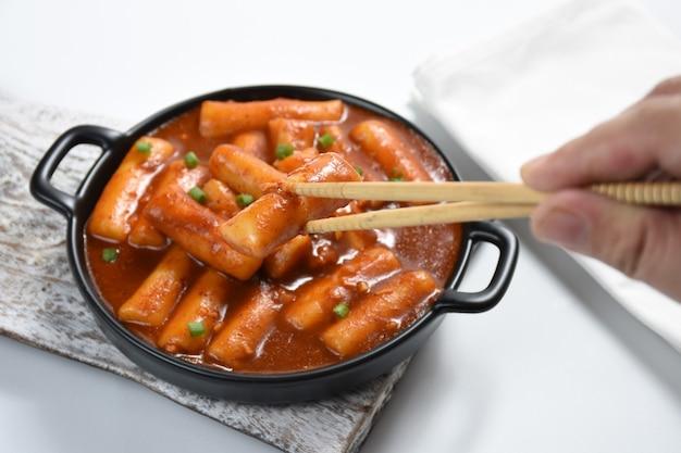 Tteokbokki oder koreanischer würziger reiskuchendas bild von köstlichen würzigen tteokbokki auf weißem hintergrund