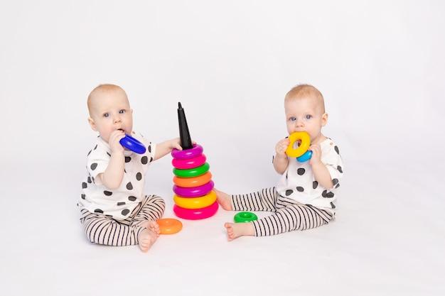 Ttwin-babys spielen auf einer weißen, isolierten, frühen entwicklung von kindern bis zu einem jahr