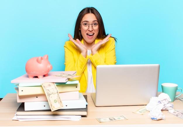 Tty geschäftsfrau sitzt auf ihrem schreibtisch und arbeitet mit einem laptop