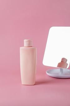 Tube mit kosmetischer creme, gesichtsprodukt, leere flaschenverpackung für die hautpflege auf rosafarbenem hintergrund. beauty- und spa-konzept.