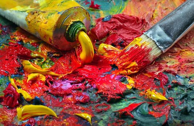 Tube mit kunstölfarbe und pinsel auf eine palette.