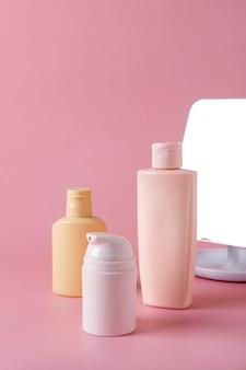 Tuben mit kosmetischer creme, gesichtsprodukt, leere flaschenverpackung für die hautpflege auf rosafarbenem hintergrund. beauty- und spa-konzept.