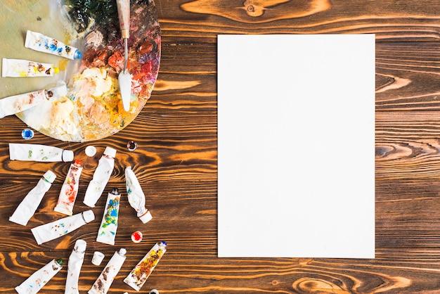 Tuben und palette in der nähe von papier