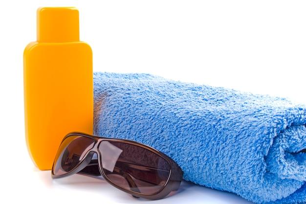 Tuch, sonnenbrille und lotionsnahaufnahme auf weißem hintergrund