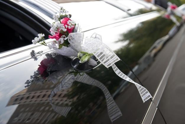 Tür des schwarzen hochzeitsautos mit blume und band