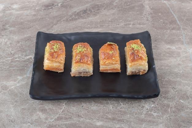 Türkische bakhlavas auf einer schwarzen platte auf marmoroberfläche