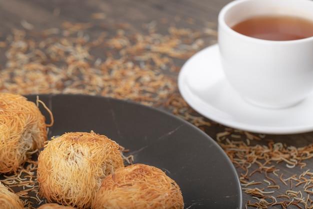 Türkische desserts mit einer weißen tasse heißen tees auf einem holztisch.