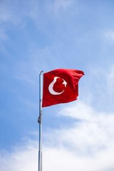 Türkische flagge, die in den wind am blauen himmel wellenartig bewegt