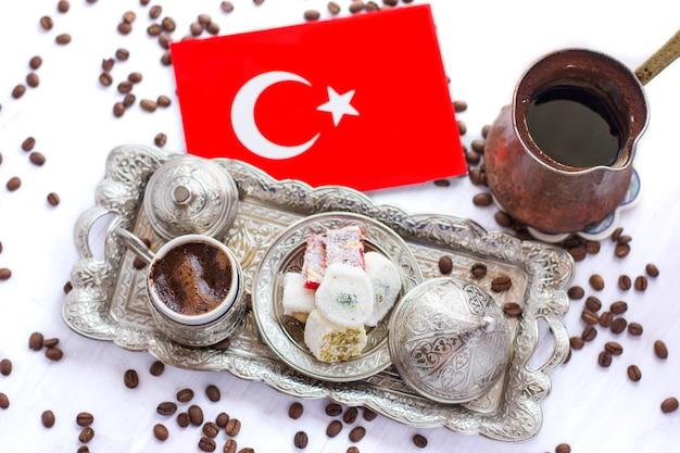 Türkische flagge neben traditionellem türkischem kaffee, süßigkeiten und jezve