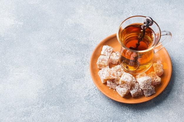 Türkische freude mit haselnuss in geschnitzter metallschüssel und tee in glasschale