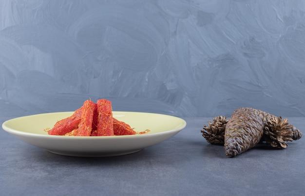 Türkische freude rahat lokum mit pistazien auf gelbem teller über grauem hintergrund.