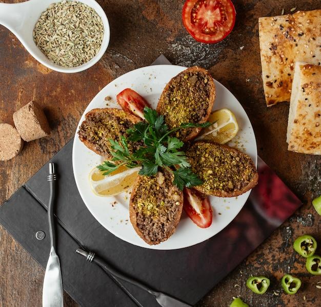 Türkische gefüllte fleischbällchen ichli kofte serviert mit zitrone, petersilie und tomate