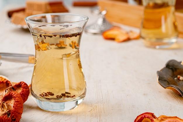 Türkische gllass tasse tee serviert mit desserts auf dem tisch