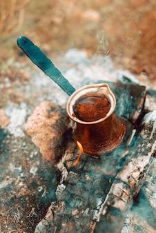 Türkische kaffeekanne auf etwas holz, das mit kaffee im inneren brennt