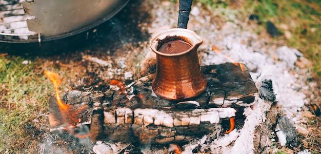 Türkische kanne mit kaffee darin auf einem brennenden holz
