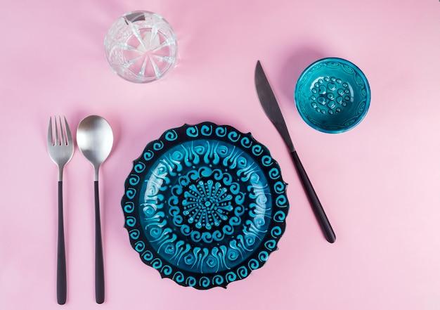 Türkische keramik verzierte blaue platte mit neuem schwarzem luxustischbesteck auf rosa, draufsicht