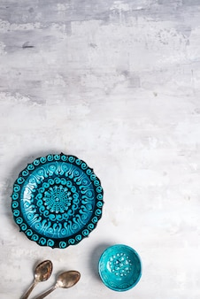 Türkische keramik verzierte blaue platte und schüssel mit löffeln auf steinhintergrund, draufsicht