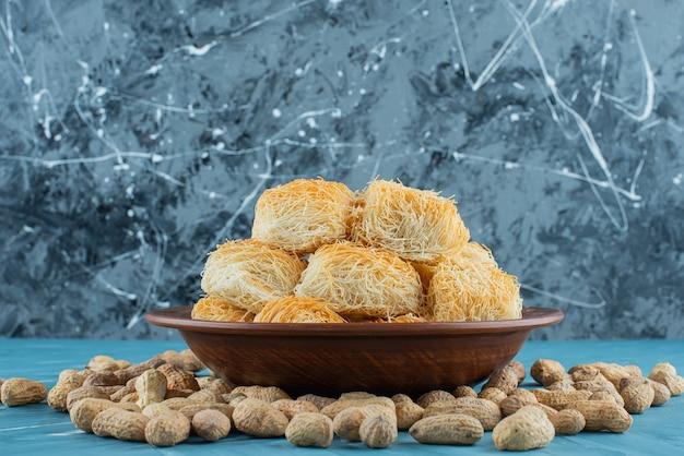 Türkische köstlichkeiten mit erdnussnüssen auf einem dunklen holzteller.