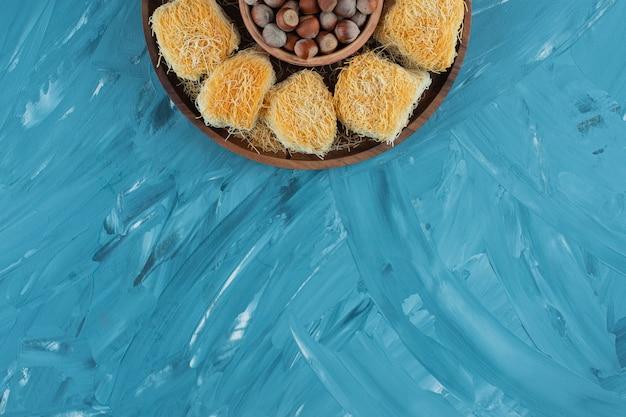 Türkische köstlichkeiten mit macadamianüssen auf einem dunklen holzteller.
