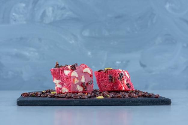 Türkische köstlichkeiten und rosinen auf dem schneidebrett auf marmortisch.