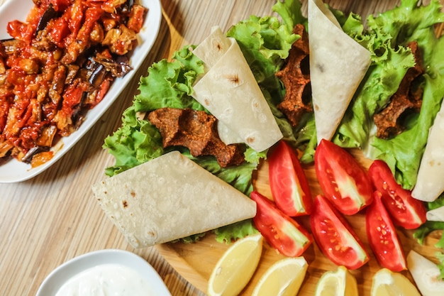 Türkische kofte mit tomate, zitrone, lavash und salat