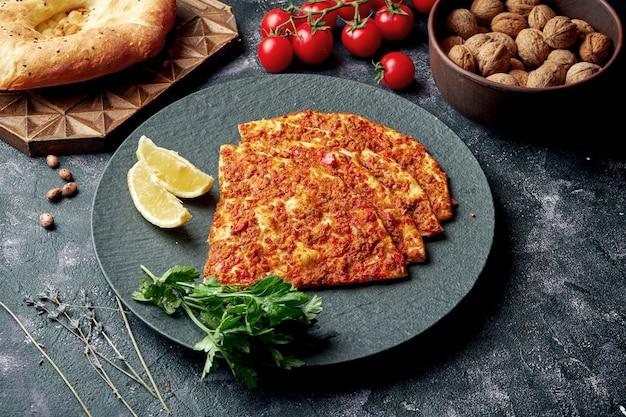 Türkische küche gericht - pide mit hackfleisch und tomaten auf einem schwarzen teller. türkisches lahmajun, nahaufnahme,
