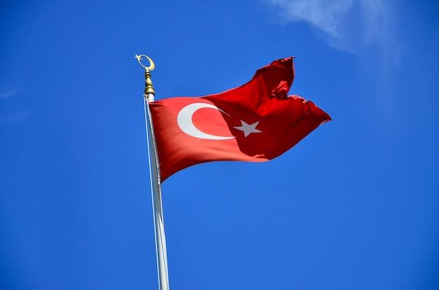 Türkische markierungsfahne, die in blauen himmel, istanbul, die türkei wellenartig bewegt