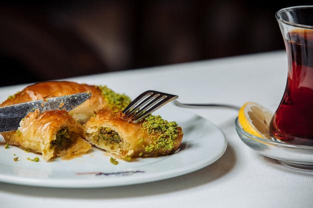 Türkische pakhlava mit pistazien serviert mit schwarzem tee