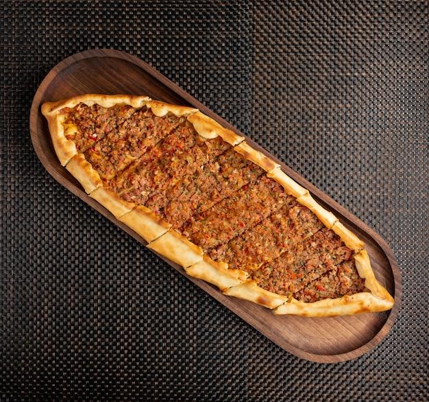 Türkische pide mit angefülltem fleisch und peperoni auf einer hölzernen schüssel